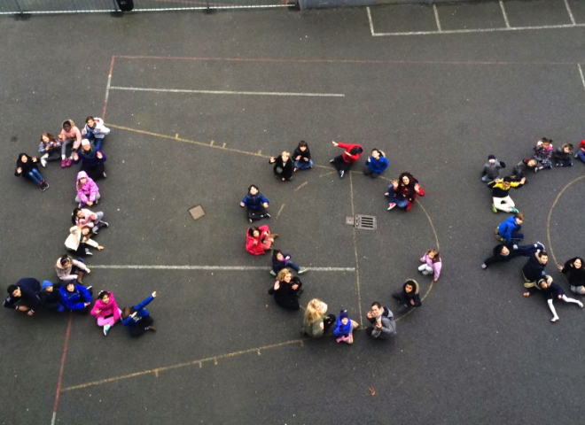 Children together creating the shape of the number 100